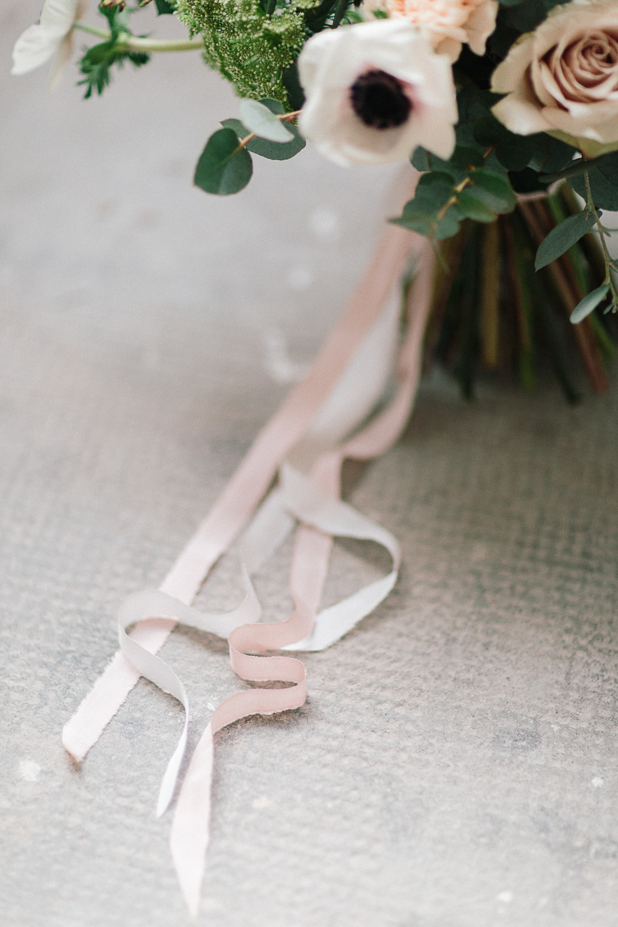 ruban rose en soie attaché autour d'un bouquet de fleurs posé sur sol béron mariage romantique industriel