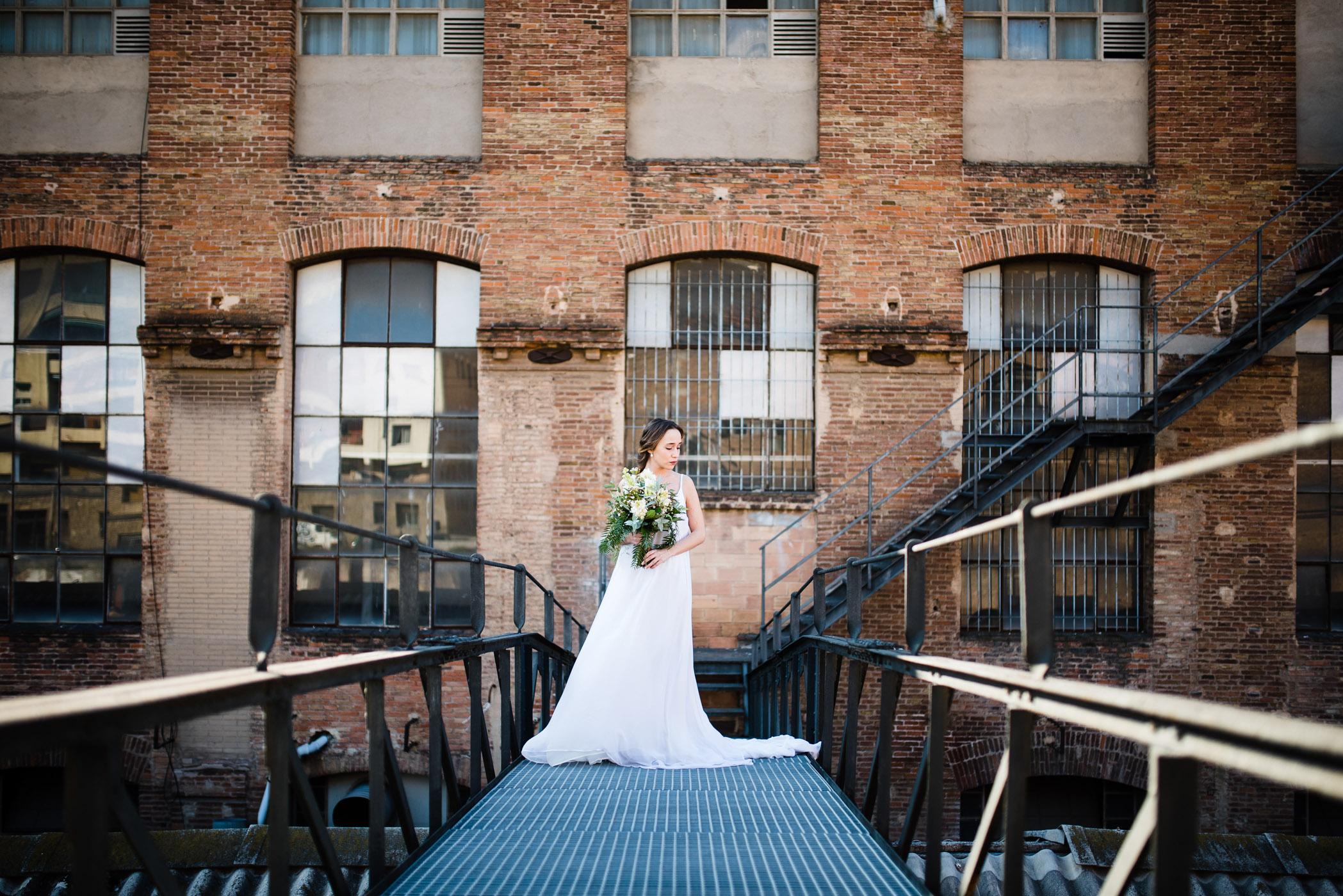 inspiration mariage industriel mariée avec bouquet de fleurs devant usine